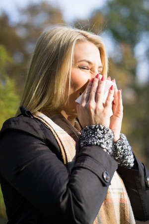 sneezing: blonde woman sneezing in tissue