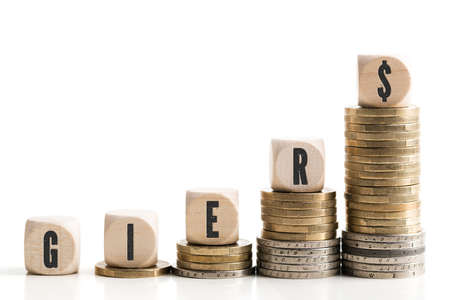 greed: Coin stacks symbolizing greed (with the German word for greed on the cubes) Stock Photo