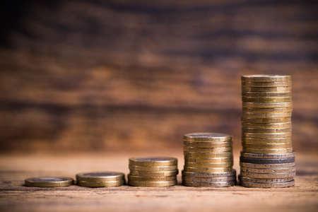 salarios: monedas apiladas que muestra un gráfico del crecimiento overproportional