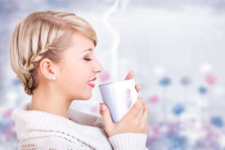 smiling woman in winter clothes drinking hot beverage