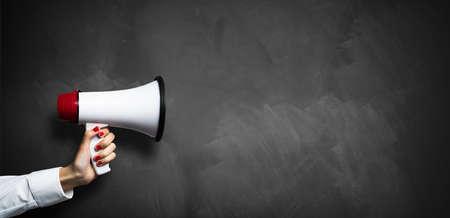 hand met een megafoon voor een leeg schoolbord