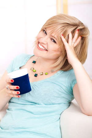 young blond woman on a couch with a cup