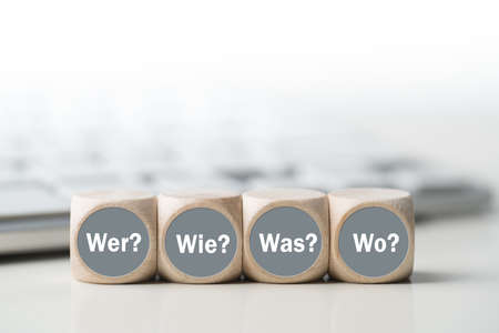 cubes with the words who, how, what, when in front of a keyboard in German