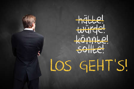 stroked: businessman standing in front of a chalkboard with stroked words like could and should and Lets go in German
