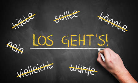 stroked: chalkboard with stroked words like could and should and Lets go in the middle in German