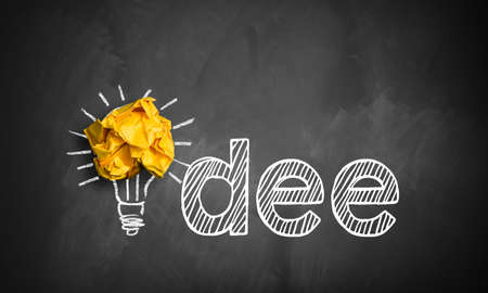 jolt: word idea (in German) on a blackboard with a lightbulb and crumpled paper as a symbol Stock Photo