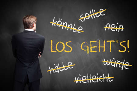 businessman standing in front of a chalkboard with stroked words like could and should and Lets go in the middle in German Stock Photo