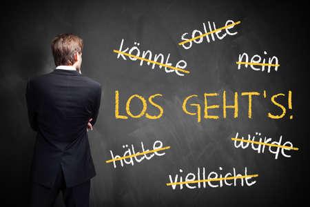 """Geschäftsmann vor einer Tafel mit strich Wörter wie könnte stehen und sollte, und in der Mitte in der deutschen """"Lass uns gehen"""" Standard-Bild - 66191195"""