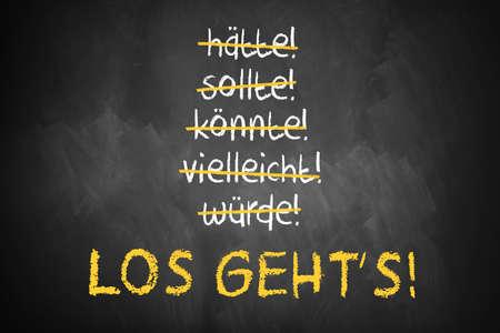 """Bord met streelde woorden als zou kunnen en moeten en """"Let's go"""" in het midden in het Duits"""
