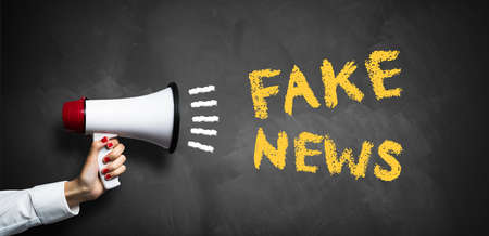 """hand with megaphone and the message """"fake news"""""""