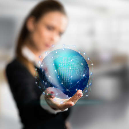 businesswoman presenting a holographic globe in front of an office scene