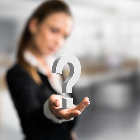 businesswoman presenting a questionmark as symbol for a concern Stock Photo