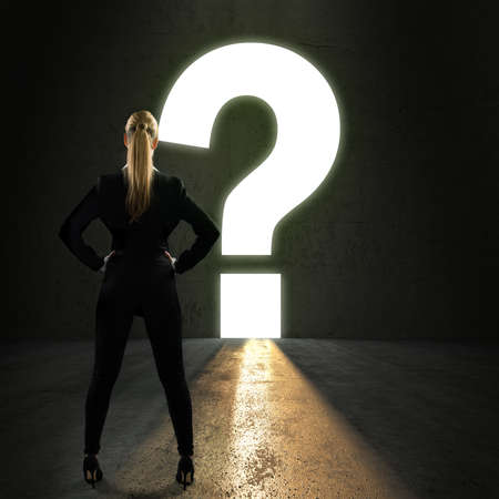 businesswoman standing in front of a portal shaped as a questionmark Stock Photo