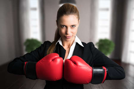 attractive businesswoman with boxing gloves ready for a fight in front of an apartment Stock Photo