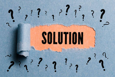 revealing: torn paper revealing the word solution Stock Photo