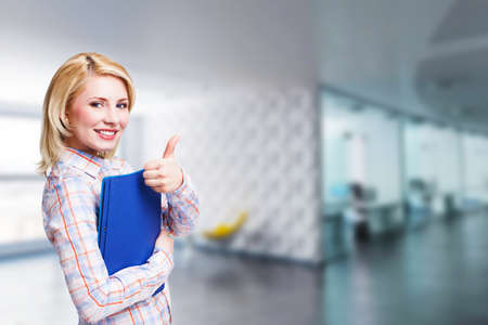 attractive blonde  businesswoman in front of an office scene Stock Photo