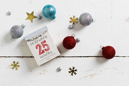tear-off calendar with 25th of december on top and christmas decoration on a wooden surface