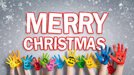 painted children hands with smiley in front of christmas background with Merry christmas message