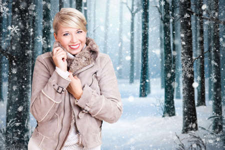 attractive blonde woman with winter clothes in front of a winter forest scene