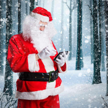 Santa Claus looking at a tablet in front of a winter scene