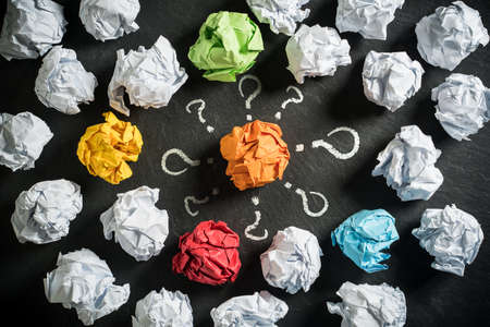 crumpled paper symbolizing different solutions with one standing out in the middle surrounded by questionmarks