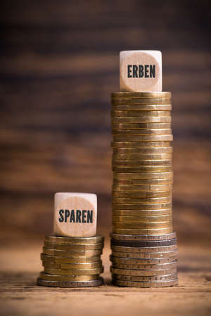 stacked coins showing unjust difference between saving money and inheriting it with the German words for save and inherit