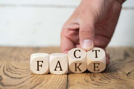 """hand onthult dat een """"feit"""" een """"nep"""" is door twee blokjes om te draaien Stockfoto"""