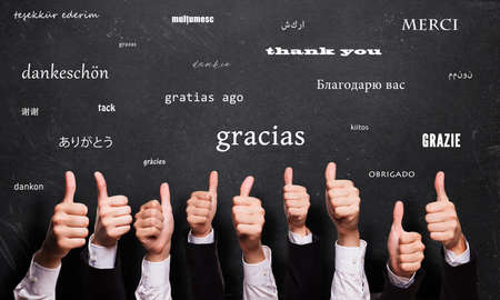 many thumbs up in front of a blackboard with the word