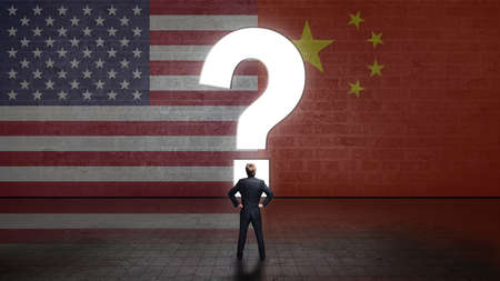 businessman standing in front of a wall with a questionmark and the flags of the usa and china