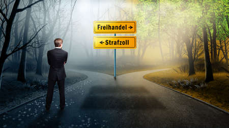 businessman standing at a crossroad having to decide between free trade and tariff (with road signs in German) Reklamní fotografie