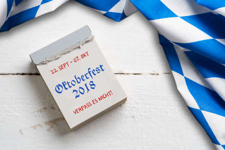 bavarian tablecloth on wooden background and a tear-off calendar with the slogan