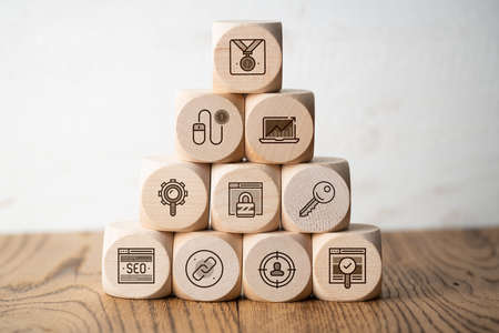 SEO strategy with components for successful marketing as icons on cubes on wooden background