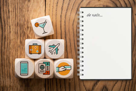 cubes with travel icons and a notebook with the words