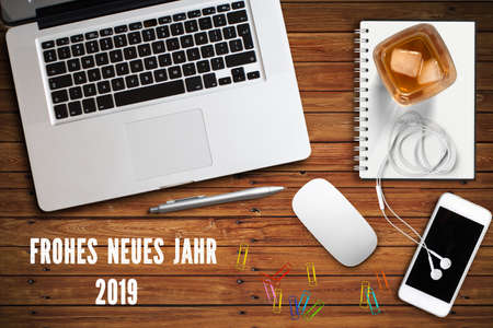 computer workspace with smartphone, a drink and the message Happy new year 2019 in German on wooden background