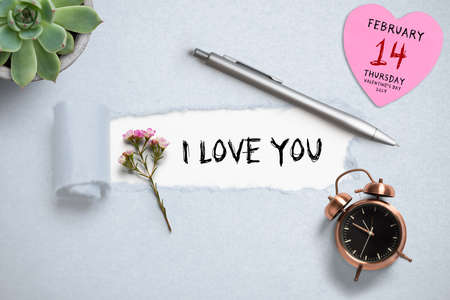 torn paper revealing the message 'I love you' surrounded by pen, flower, clock and a reminder for Valentine's Day 2019