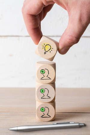 Muchas personas juntas tienen una idea simbolizada por iconos en cubos sobre fondo de madera Foto de archivo