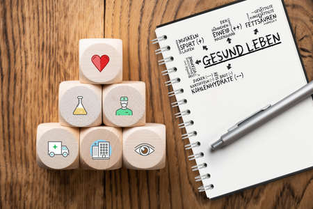 medical icons on cubes with a note pad with a plan for healthy living (in German) on wooden background