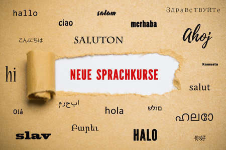 curled up paper revealing the phrase new language courses in German surrounded by the word hello in many languages Reklamní fotografie