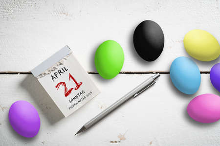 Easter Eggs tear-off calendar with April 21th 2019, Easter in German on top wooden background