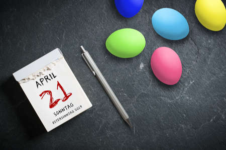 Easter Eggs tear-off calendar with April 21th 2019, Easter in German on top on slate background 스톡 콘텐츠