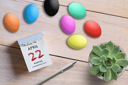 Easter Eggs tear-off calendar with April 22nd 2019, Easter Monday in German on top on wooden background