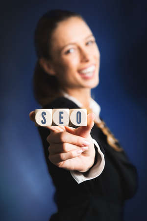 woman holding cubes with the acronym SEO for search engine optimization