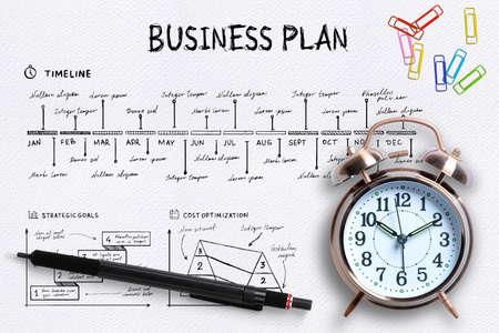Nahaufnahme von oben auf einen professionellen Schreibtisch mit Wecker, farbigen Büroklammern und einem Stift auf einem komplexen schriftlichen Geschäftsplan mit Kopierraum