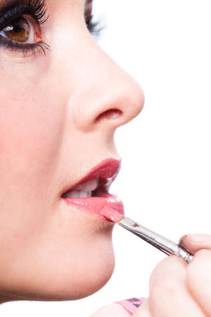 Beauty and glamour concept with woman applying pink lip gloss with an applicator in a close up cropped face portrait on white