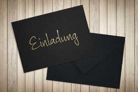 Invitation in German handwritten on a black envelope and card lying on a wood table viewed from above
