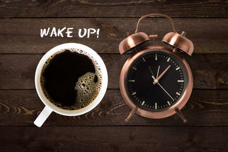 Mug of coffee and classical copper colored alarm clock with bells in a Wake Up concept on a wooden table with text