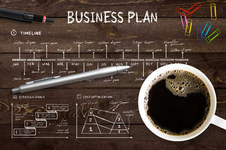 Close-up view from above of a professional desk with a cup full of hot coffee, colored paper clips and a pen on a complex written business plan with copy space