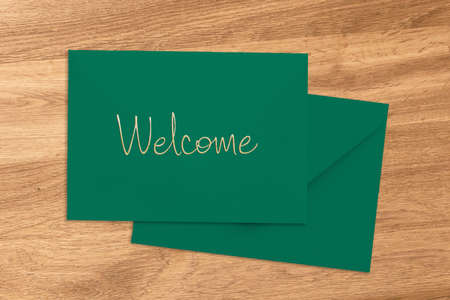 Welcome greeting handwritten on a green envelope and card lying on a wood table viewed from above