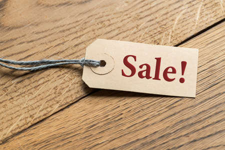 Hangtag with the word SALE! on wooden background