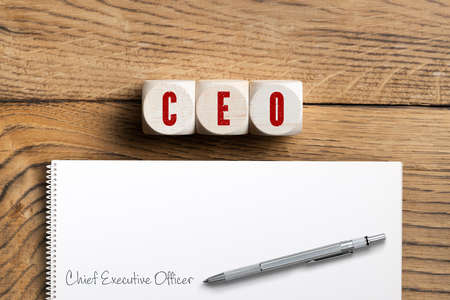CEO spelled in red on three wooden blocks next to paper with pens on wood surface